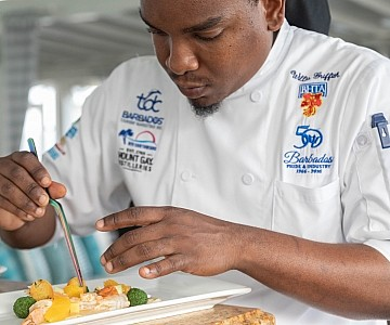 Chef plating a meal in Barbados hotel photo shoot