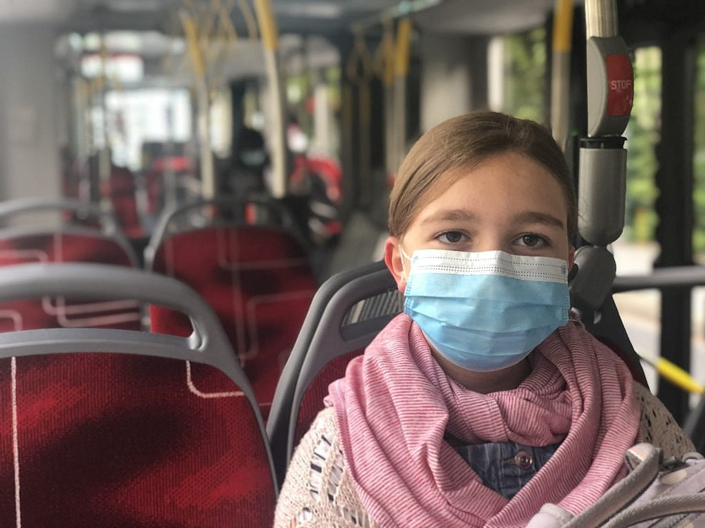 Photograph of Sienna on the bus wearing a face mask